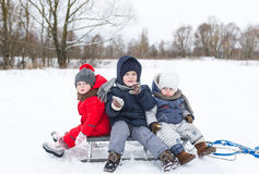 Three children sit on the sledge in winter day. Royalty Free Stock Photography