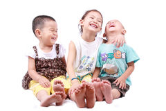 Three children sitting. Three happy laughter of children sitting on a white background stock photography