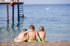 Three children sitting on a beach Stock Photos