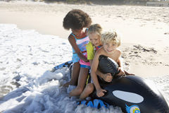 Three children (5-10) sitting on inflatable toy whale on beach, playing in surf, smiling Stock Image