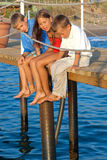 Three Children Sitting On The Pier. Stock Images
