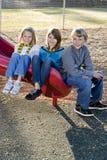 Three children sitting on slide Royalty Free Stock Images