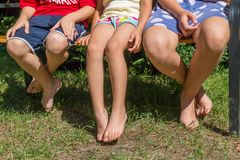 Three children sitting together on bench royalty free stock photography