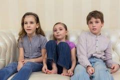 Three children sitting and watching TV. Three children sitting on a sofa and watching TV stock images