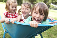 Three Children Sitting In Wheelbarrow Royalty Free Stock Image