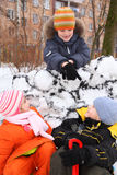Three children at snow fortress in yard Stock Photography
