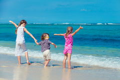 Three children standing on the beach Stock Images