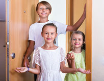 Three children standing at house entrance Stock Photo