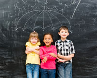 Three children standing under drawn umbrella Stock Images
