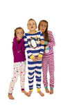 Three children standing wearing Christmas pajamas frightened exp Royalty Free Stock Photography