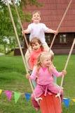 Three children on swing royalty free stock photos