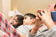 Three children with their electronic gadgets at bedtime. stock images