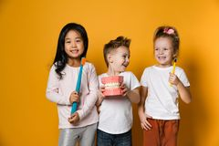 Dental hygiene. happy little cute children with toothbrushes. Three children with toothbrushes and a kissuos mock-up with zooms stand over yellow background stock photos