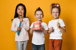 Dental hygiene. happy little cute children with toothbrushes. Three children with toothbrushes and a kissuos mock-up with zooms stand over yellow background stock photo