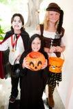 Three Children - Trick or Treat. Three kids in Halloween costumes going trick or treating door-to-door. Focus on little boy in front stock images