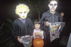 Three children trick or treating for Halloween in Oak View, CA Royalty Free Stock Images