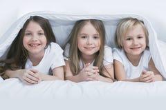 Three children under blanket Stock Photos