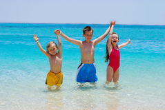 Three Children Wading in Ocean. Three small children stand with their hands linked and arms raised above their heads. Children are wading into a tropical ocean stock image