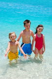Three Children Wading in Ocean Stock Image