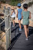 Three children on a walkway on the beach. royalty free stock image