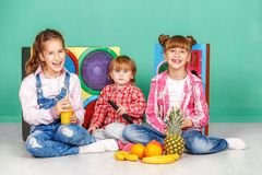 Three children watch tv and eat fruits. The concept of a healthy. Lifestyle, food, childhood, vitamins, vegetarianism Royalty Free Stock Photo