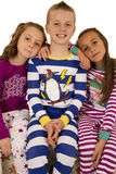 Three children wearing winter pajamas sitting smiling happy Stock Photo