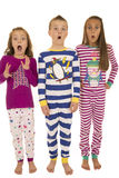 Three children wearing winter pajamas with a startled facial exp Stock Photos