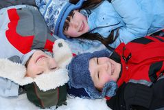 Three Children in Winter. Three children lying in the snow in winter hats and jackets Royalty Free Stock Photography