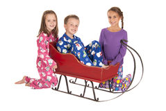 Three children in winter pajamas around a sleigh Royalty Free Stock Images