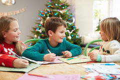 Three Children Writing Letters To Santa Together Royalty Free Stock Image