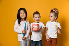 Three childrens with toothbrushes and a kissuos mock-up with zooms stand over yellow background
