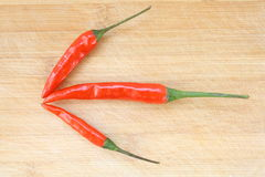 Three chili peppers on wood Royalty Free Stock Images