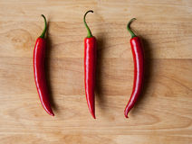 Three chilli peppers on wood Stock Images