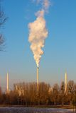 Three chimneys. Of a German power-plant, one of them smoking into the clear blue winter sky of Karlsruhe with a lake in the foreground Royalty Free Stock Photography