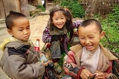 Three Chinese children having fun near the farmhouse, Basha Miao Village, Congjiang County, Southeast Guizhou Province, Southwest royalty free stock photo