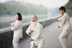 Three Chinese People Practicing Tai Ji Outdoors stock photos
