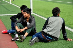 Pengzhou, China: Three Youths Watching Sports. Three Chinese teenage boys sitting on the Astroturf at the local sports stadium watching nearby basketball and Stock Image