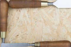 Three chisels on a wooden background. Professional chisels on a wood background. Visible wood grain Royalty Free Stock Photos