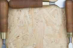 Three chisels on a wooden background. Professional chisels on a wood background. Visible wood grain Royalty Free Stock Photography