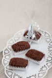 Three Chockolate Brownie on wooden kitchen board. Chocolate cookies in decorative boxes on a white ornamental table-cloth (napkin royalty free stock photography