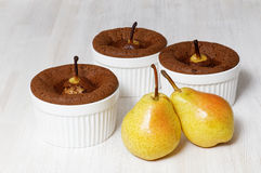 Three chocolate-almond muffins with pears in white ceramic baking dish Stock Photos