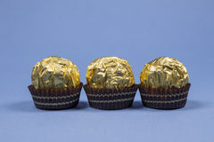 Three chocolate candy wrapper. Three chocolates in the baskets and the Golden wrapper Stock Images