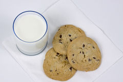 Three chocolate chip cookies and glass of milk Royalty Free Stock Image