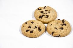 Three chocolate chip cookies sweet and good to eat. A cookie is a baked or cooked food that is small, flat and sweet. It usually contains flour, sugar and some Royalty Free Stock Photography