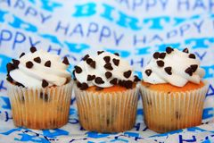 Three chocolate chip cupcakes on happy birthday background royalty free stock images