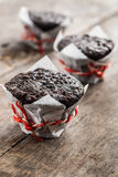 Three chocolate cupcake muffin on a wooden table Royalty Free Stock Photos
