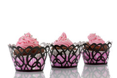 Three Chocolate cupcakes with pink butter icing Royalty Free Stock Images