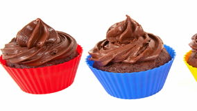 Three Chocolate Cupcakes. In red blue and yellow holders stock footage