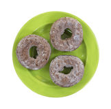 Three chocolate donuts on green plate Stock Photo