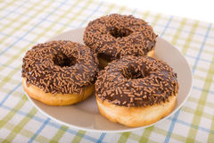 Three chocolate donuts with sprinkles on plate Stock Image